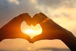 two hands put together in a heart shape with the sun going through it representing two people spreading love through service