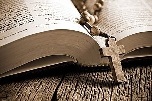 a wooden rosary resting in a Holy Bible to demonstrate living by the Bible and going to church on Sundays