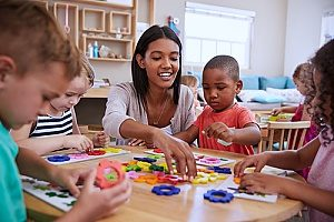 a preschool teacher with students at a Christ Lutheran preschool who are learning how to make arts and crafts