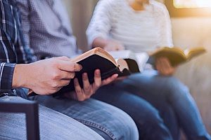 two churchgoers reading from the bible as they attend Sunday worship to improve their mental health