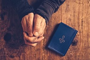 a man crossing is hands with a holy bible next to him while he is participating in sunday worship services