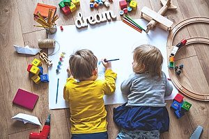 two toddlers who are brother and sister at a Christian preschool drawing on a large sheet of paper while surrounded by toys